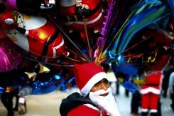 A migrant in the Santa Claus costume sells balloons at Ledra, a main shopping street of capital Nicosia, Cyprus, Saturday, Dec. 20, 2014, during the Christmas celebrations. (AP Photo/Petros Karadjias)