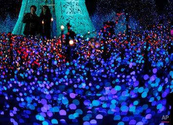 People enjoy an annual year end illumination in Shiodome district in Tokyo, Japan, Monday, Nov. 24, 2014. (AP Photo/Shuji Kajiyama)