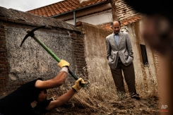 In this photo taken on July 19, 2014, a man looks at an excavation as an A.R.M.H., Association for the Recovery of Historical Memory, volunteer digs on the search for the body of Perfecto de Dios, in a hidden grave in Chaherrero, Spain. (AP Photo/Daniel Ochoa de Olza)