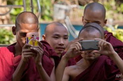 Buddhist monk take pictures at a courthouse as they await to see New Zealand citizen Philip Blackwood after a court hearing in Yangon, Myanmar, Thursday, Dec. 18, 2014. Blackwood, general manager of the V Gastro Bar, and two Myanmar business partners have pleaded innocent to charges they insulted religion by posting an advertisement with an image of a pink Buddha wearing headphones. (AP Photo/Gemunu Amarasinghe)