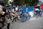 Anti-government demonstrators fall to the ground during clashes with national police officers during a protest calling for the resignation of Haiti's President Michel Martelly in Port-au-Prince, Haiti, Tuesday, Dec. 16, 2014. Haiti's capital has endured a growing number of demonstrations in recent weeks during which protesters have demanded the holding of elections that were expected in 2011 and the resignations of Prime Minister Laurent Lamothe as well as President Michel Martelly. Lamothe resigned over the weekend. (AP Photo/Dieu Nalio Chery)