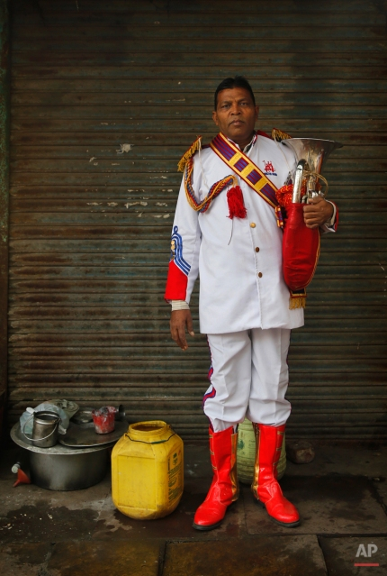 In this Friday, Nov. 28, 2014. photo, Mohammad Gore from Sambal, some 160 kilometres (100 miles) from Delhi, a members of Master Band, an Indian brass band specialized in playing weddings, poses for a portrait in New Delhi. (AP Photo/Manish Swarup)