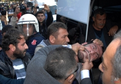 Plain clothed police officers detain a man who was trying to set up a tent to mourn and commemorate the fighters killed in Syrian city of Ayn al-Arab or Kobani, in southern Turkish city of Adana, Turkey, Monday, Dec. 15, 2014. (AP Photo/Hurriyet)