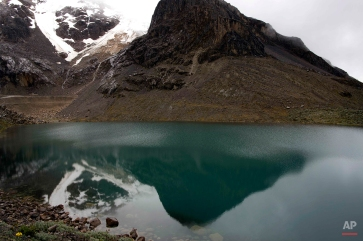 The Contrayerba glacier is reflected in a lagoon in the Huascaran National Park in Huaraz, Peru, Wednesday, Dec. 3, 2014. Peru's glaciers have lost more one-fifth of their mass in just three decades, and the 70 percent of Peru's 30 million people who inhabit the country's Pacific coastal desert, depend on glacial runoff for hydropower and to irrigate crops, meaning their electricity and long-term food security could also be in peril. Higher alpine temperatures are killing off plant and animal species in cloud forests and scientists predict Pacific fisheries will suffer. (AP Photo/Rodrigo Abd)