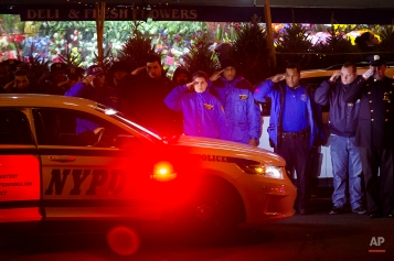 Mourners stand at attention as the bodies of two fallen NYPD police officers are transported from Woodhull Medical Center, Saturday, Dec. 20, 2014, in New York. An armed man walked up to two New York Police Department officers sitting inside a patrol car and opened fire Saturday afternoon, killing both officers before running into a nearby subway station and committing suicide, police said. (AP Photo/John Minchillo)