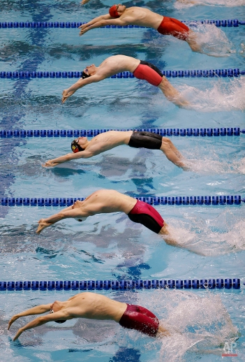 Competitors in the 12th heat of the men's 100-yard backstroke push off the starting blocks during the morning preliminaries at the Winter National Swimming Championships in Greensboro, N.C., Friday, Dec. 5, 2014. (AP Photo/Bob Leverone)