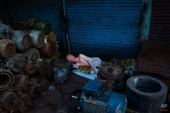 An albino man sleeps surrounded by piles of equipment in New Delhi, India, Tuesday, Aug. 26, 2014. Many laborers in the Indian capital have no permanent residence and are forced to sleep in the streets. (AP Photo/Bernat Armangue)