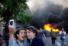 Tourists take a 'selfie' picture as demonstrators burn a trash container during a May Day rally in Barcelona, Spain, Thursday, May 1, 2014. (AP Photo/Manu Fernandez)