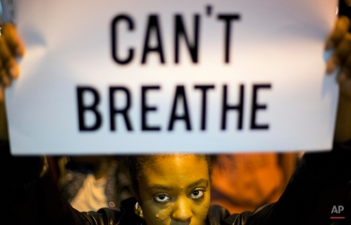 Atiya Elliott-Semper, of Atlanta, holds up a sign during a demonstration in Atlanta on Thursday, Dec. 4, 2014 against the deaths of two unarmed black men at the hands of white police officers in New York City and Ferguson, Mo. (AP Photo/David Goldman)