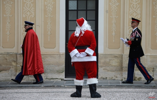 A man dressed as Santa Claus looks at Monaco Chief of staff Luc Fringant, left, and an unidentified Monaco's military officer during the traditional Christmas tree viewing and present receiving session at Monaco palace, Wednesday, Dec. 17, 2014. This event takes place every years ahead of Christmas. (AP Photo/Lionel Cironneau)