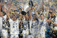 Los Angeles Galaxy's Landon Donovan, center, hoists the trophy as he and teammates celebrate after winning the MLS Cup championship soccer match against the New England Revolution Sunday, Dec. 7, 2014, in Carson, Calif. (AP Photo/Jae C. Hong)