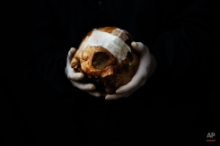 In this photo taken on Dec. 16, 2014, a volunteer holds a repaired skull before placing it inside a box during an exhumation of a mass grave at the cemetery of Puerto Real, Spain. (AP Photo/Daniel Ochoa de Olza)