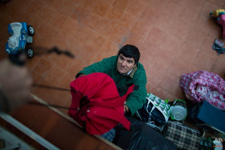 Aristides Apolo, 58 years old and unemployed, passes his belongings to his friend, Israel Plaza, as he prepares to leave after the police surrounded the apartment to evict him and his partner, in Madrid, Spain, Monday, Dec. 15, 2014. The landlord's loss of the apartment to a Bankia bank caused Apolo and his partner Mercedes Pincay's eviction. Apolo, lived with 50 year old Pincay, in a foreclosed apartment that was owned by her sister who stopped paying her mortgage fees. Pincay and Apolo remained in the apartment as they could not afford to pay rent due to their financial situation as well as health issues as Pincay is recovering from breast cancer. The eviction was carried out. (AP Photo/Andres Kudacki)