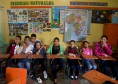 In this Thursday, Nov. 27, 2014 photo, Roberto Castellanos, fourth from left, poses for a photo with friends inside a class room at his school in Tegucigalpa, Honduras. His parents didn't ask Roberto to get a job, but they are proud of his hard work and appreciate his contribution to the family. (AP Photo/Esteban Felix)