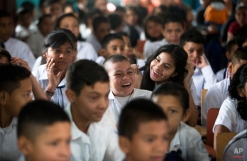 """In this Saturday, Nov. 29, 2014 photo, Roberto Castellanos, center, smiles with friends during a graduation ceremony at his school in Tegucigalpa, Honduras. His teacher says he gets almost perfect grades, and in a country where only one in four children finishes secondary school, Roberto says he wants to study to be a lawyer so he might one day """"defend the good people against the bad people."""" (AP Photo/Esteban Felix)"""