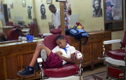 Jose Luis, 7, in his school uniform, falls asleep in a barber's chair, while waiting for his father's work shift to end, in Old Havana, Cuba, Tuesday, May 21, 2013. (AP Photo/Ramon Espinosa)