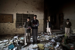 Pakistani students, Waqar Ahmad, left, and Uwais Naser, who survived last Tuesday's Taliban attack on a military-run school, stand at the site, one holding a picture of their headmaster Tahira Kazi, 58, who was killed in the attack, in Peshawar, Pakistan, Thursday, Dec. 18, 2014. (AP Photo/Muhammed Muheisen)