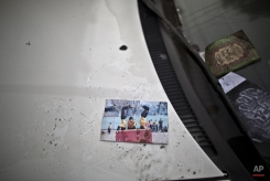 A picture showing schoolchildren playing is left on a car, inside the Army Public School attacked last Tuesday by Taliban gunmen, in Peshawar, Pakistan, Thursday, Dec. 18, 2014. (AP Photo/Muhammed Muheisen)
