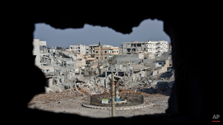 This Nov. 20, 2014 photo shows an area controlled by the Islamic State group, past the Qada Azadi roundabout, foreground, in Kobani, Syria. Amid the wasteland and destroyed buildings, a sense of camaraderie has developed among the town's defenders who have doggedly fought off militant advances for more than two months. (AP Photo/Jake Simkin)
