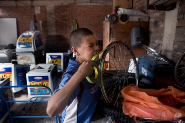 In this Tuesday, Nov. 25, 2014 photo, Roberto Castellanos works repairing a bicycle wheel of an ice cream cart at a bicycle repair shop in Tegucigalpa, Honduras. Roberto's curved biceps and calloused hands are the result of his previous job in construction. About six months ago, Fernando Saravia gave in to Roberto's persistent appeals and offered him a job in the workshop. After his mother checked out the shop and met the boss, Roberto accepted. (AP Photo/Esteban Felix)