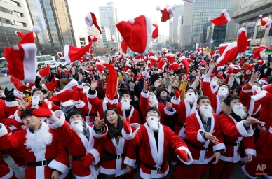 Volunteers clad in Santa Claus costumes throw their hats in the air as they gather to deliver gifts for the poor in downtown Seoul, South Korea, Wednesday, Dec. 24, 2014. (AP Photo/Ahn Young-joon)