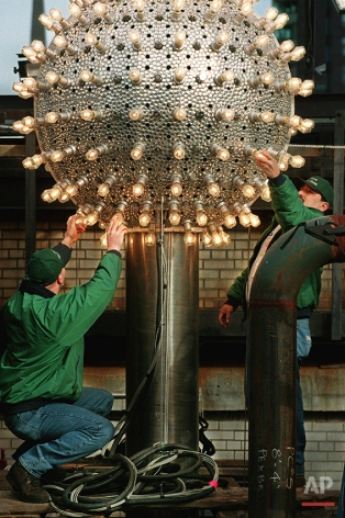 Electricians Brian Sperazza, left, and Carlos Freire replace burned out bulbs on the Times Square New Year's Eve ball in New York, Wednesday, Dec. 30, 1998 during a dress rehearsal for tomorrow night's New Year's Eve festivities. A tradition originated by The New York Times in 1907, the lowering of the lighted ball in Times Square has become a universal symbol of ushering in the New Year. (AP Photo/Kathy Willens)