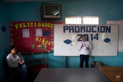 In this Saturday, Nov. 29, 2014 photo, Roberto Castellanos poses for a picture with his diploma after a graduation ceremony at his school in Tegucigalpa, Honduras. (AP Photo/Esteban Felix)