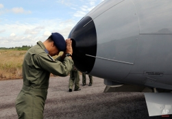 A crew member of Indonesian Navy CN-235 airplane prays prior to the start of a search operation for the missing AirAsia flight 8501 at the airport in Pangkal Pinang, Bangka Island, Indonesia, Tuesday, Dec. 30, 2014. Six bloated bodies and debris seen floating in Indonesian waters Tuesday painful ended the mystery of AirAsia Flight 8501, which crashed into the Java Sea and was lost to searchers for more than two days. (AP Photo/Tatan Syuflana)