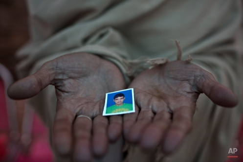 Pakistani Sayed Shah, shows a picture of his son Zulqarnain, 17, a student who was killed in last Tuesday's Taliban attack on a military-run school, in Peshawar, Pakistan, Thursday, Dec. 18, 2014. (AP Photo/Muhammed Muheisen)