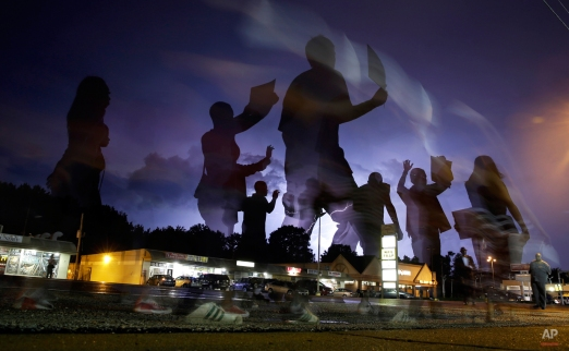 Protesters march in the street as lightning flashes in the distance in Ferguson, Mo. on Wednesday, Aug. 20, 2014. On Aug. 9, 2014, a white police officer fatally shot Michael Brown, an unarmed black 18-year old, in the St. Louis suburb. (AP Photo/Jeff Roberson)