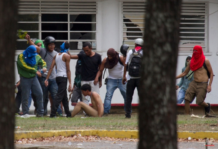 In this April 3, 2014 photo, government supporters beat a naked opposition student as he's forced to sit on the ground inside of the Central University of Venezuela, UCV, during an anti-government protest in Caracas, Venezuela. Students attempted to march from the university to protest the country's deteriorating economy, but hundreds of riot police prevented them from leaving campus, deploying tear gas and flash-bang grenades. The hours-long street battle ended with pro-government groups in bandanas storming the campus. (AP Photo/Fernando Llano)