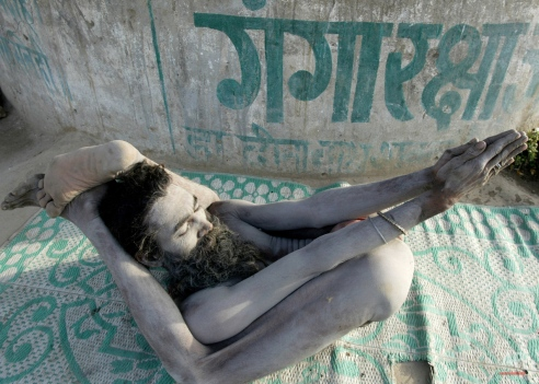 """An Indian Naga Sadhu, or Hindu holy man, performs yoga exercises on the banks of the River Ganges during the Magh Mela in Allahabad, India, Thursday, Feb. 16, 2006. Written on wall in background is """"Gangaraksha,"""" or Ganga Protection. (AP Photo/Rajesh Kumar Singh)"""