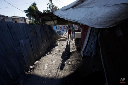 A man walks in a neighborhood in Port-au-Prince, Haiti, Thursday, Jan. 14, 2010. A 7.0-magnitude earthquake struck Haiti Tuesday. (AP Photo/Gregory Bull)