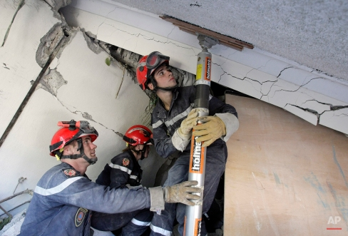 French military rescuers work to secure a structure at the collapsed Montana Hotel in Port-au-Prince, Haiti, Friday, Jan. 15, 2010. A powerful earthquake struck Haiti Tuesday. (AP Photo/Francois Mori)