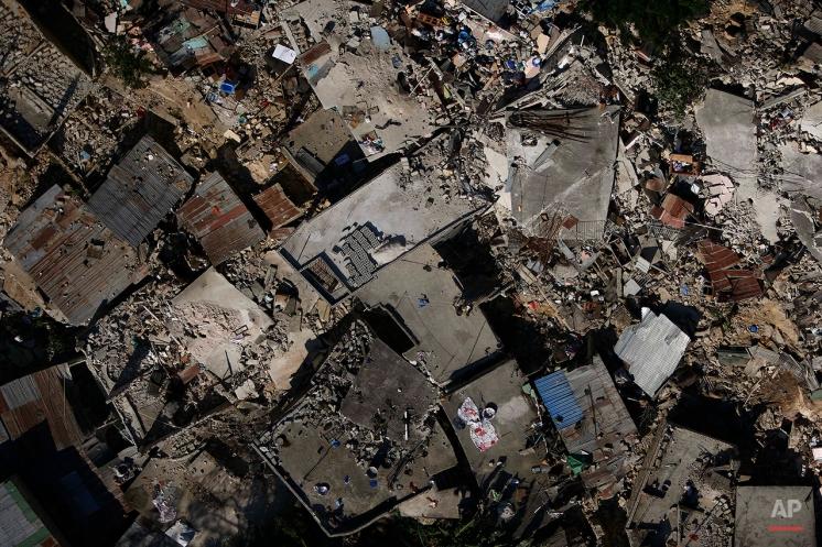 Homes lay in ruins due to an earthquake in Port-au-Prince, Haiti, Friday, Jan. 15, 2010. (AP Photo/Ricardo Arduengo)