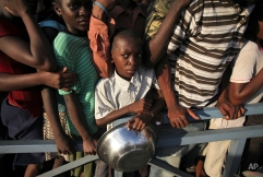 A young earthquake survivor holds a bowl as he waits in line for high protein biscuits from the World Food Program in Port-au-Prince, Saturday, Jan. 16, 2010. (AP Photo/Ariana Cubillos)