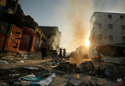 People walk through fire and rubble in the market area in Port-au-Prince, Monday, Jan. 18, 2010. (AP Photo/Gerald Herbert)