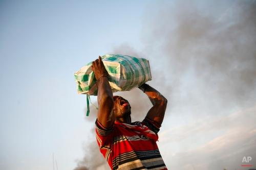 An earthquake survivor drinks juice dripping from a stolen bag in Port-au-Prince, Tuesday, Jan. 19, 2010. (AP Photo/Ricardo Arduengo)