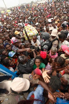 Haitians surge the gates at a food distribution point in the Cite Soleil neighborhood in the aftermath of the Jan. 12 earthquake in Port-au-Prince, Tuesday, Jan. 26, 2010. (AP Photo/Gerald Herbert)