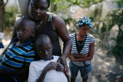 In this photo taken Tuesday, Feb. 2, 2010, Tulia Ulysse hugs her son Emmanuel, left, and nephew Ulise at her home in Gros Morne, about 105 miles (170 km) northeast of Port-au-Prince. (AP Photo/Rodrigo Abd)