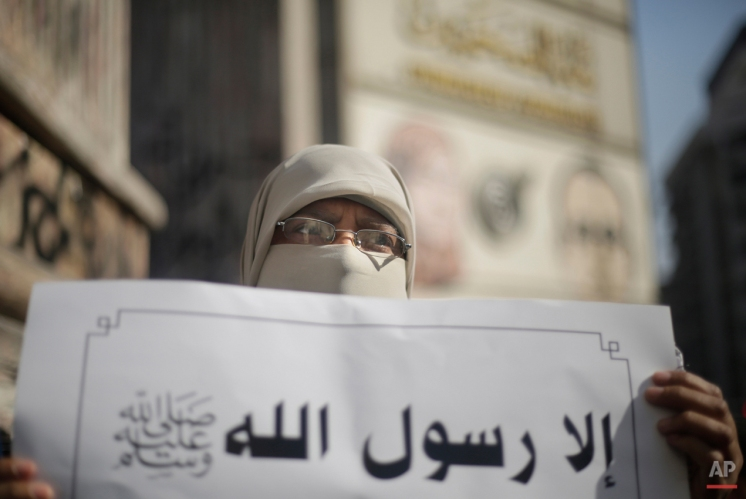 """An Egyptian protester holds a banner in Arabic that reads, """"except God's prophet, peace be upon him,"""" during a protest against the satirical magazine Charlie Hebdo's latest publication of a cartoon depicting the Prophet Muhammad, in front of the Press Syndicate in Cairo, Egypt, Tuesday, Jan. 20, 2015. The attack on the French satirical newspaper has caused grief and soul-searching around the world, and exposed the risks humorists can run in an era of instant global communications and starkly opposed ideologies. (AP Photo/Amr Nabil)"""