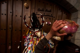 People throw turnips at the Jarramplas as he makes his way through the streets beating his drum during the Jarramplas Festival in Piornal, Spain, Tuesday, Jan. 20, 2015. (AP Photo/Daniel Ochoa de Olza)
