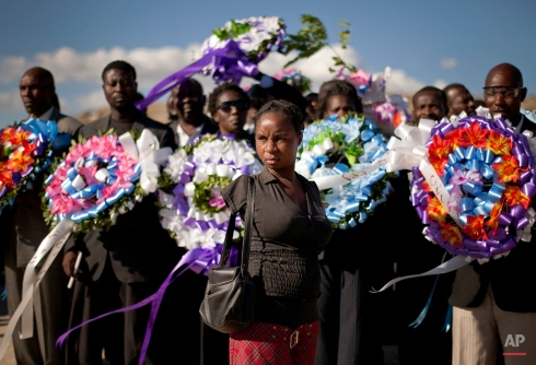 A woman who lost both her arms from injuries sustained in the 2010 earthquake and a group carrying funeral wreaths, arrive at the mass grave site in Titanyen to attend a memorial service for people who died in the 2010 earthquake, on the outskirts of Port-au-Prince, Haiti, Thursday Jan. 12, 2012. Haitians are marking the second anniversary of the devastating earthquake with church services throughout the country on what is a national holiday of remembrance. The government has said the disaster killed 316,000 people and displaced 1.5 million. More than 500,000 are still in temporary settlement camps. (AP Photo/Ramon Espinosa)