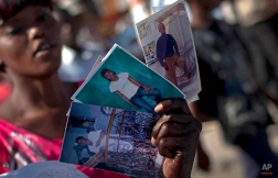 A woman holds photos of relatives who were killed in the 2010 earthquake as she prays with other faithful as they visit areas of the city where people were killed in Port-au-Prince, Haiti, Thursday Jan. 12, 2012. (AP Photo/Ramon Espinosa)