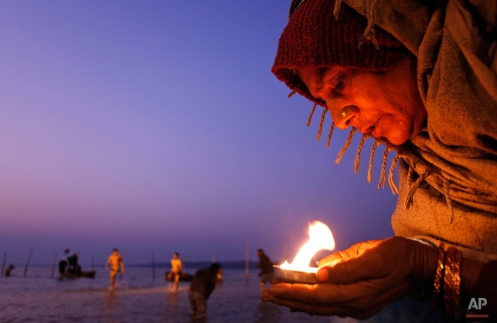 Hindu devotee holds an oil lamp and offers prayers to the Sun god at the Sangam, the confluence of the rivers Ganges, Yamuna and the mythical Saraswati, on Makar Sankranti festival, that falls during the annual traditional fair of Magh Mela, in Allahabad, India, Saturday, Jan. 14, 2012. (AP Photo/Rajesh Kumar Singh)