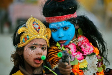 In this Sunday, Jan. 15, 2012 photo, Indian children dressed as Hindu God Shiva, right, and Parvati hold a toy gun as they pose for a photograph during the annual traditional fair of Magh Mela at the Sangam, the confluence of the rivers Ganges, Yamuna and the mythical Saraswati, in Allahabad, India, Sunday, Jan. 15, 2012. (AP Photo/Rajesh Kumar Singh)