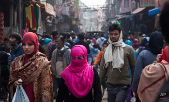 """Indian Muslim women walk on the street leading to the 17th Century Jama Masjid, the principal mosque in the city, in New Delhi, India, Tuesday, Jan. 27, 2015. U.S. President Barack Obama gently nudged India Tuesday to fulfill its constitution's pledge to uphold the """"dignity of the individual,"""" drawing on his own experience as a minority in the United States as he closed out a three-day visit to New Delhi. Equality is enshrined in India's constitution, but religious minorities and women have experienced harassment and violence. (AP Photo/Tsering Topgyal)"""