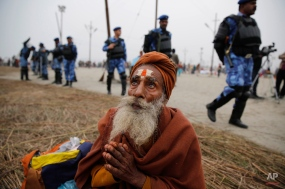 An elderly Hindu devotee prays as Rapid Action Force (RAF) soldiers patrol at Sangam, the confluence of rivers Ganges and Yamuna on Makar Sankranti festival which also marks the beginning of Magh Mela in Allahabad, India, Tuesday, Jan. 14, 2014. (AP Photo/Rajesh Kumar Singh)