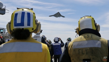Sailors watch as an X-47B Navy drone does a flyby the USS George H.W. Bush after it was launched from the ship off the coast of Virginia Tuesday, May 14, 2013. (AP Photo/Steve Helber)