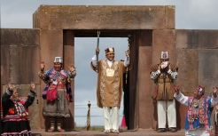Bolivia's President Evo Morales holds his sacred staffs of power in a ceremonial swearing-in, led by Aymaran spiritual guides, at the archeological site Tiwanaku, Bolivia, Wednesday, Jan. 21, 2015. Morales is set to begin a new term Thursday, that will make him the Andean nation's longest-serving leader, riding high on a wave of unprecedented growth and stability. (AP Photo/Juan Karita)
